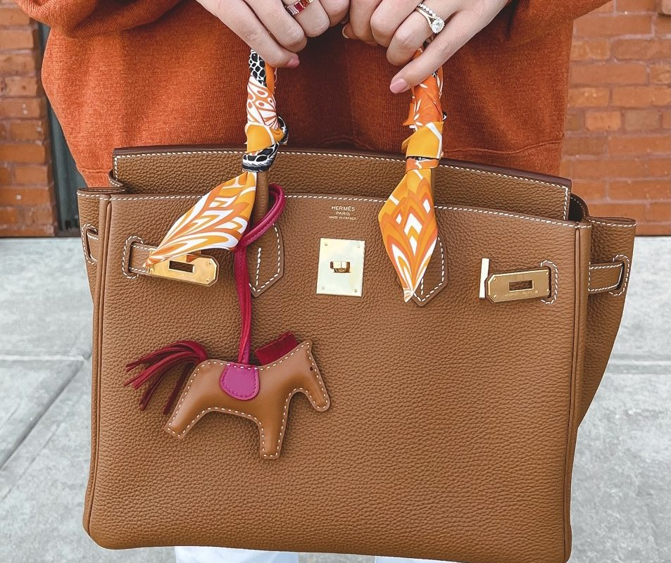 Hermes gold togo birkin with rodeo charm and orange tunic
