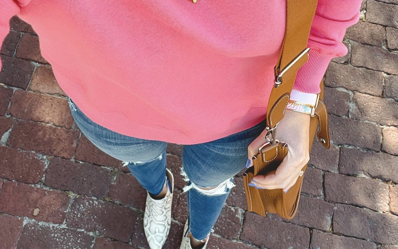 rebecca minkoff pink sweatshirt with snakeskin booties and ripped jeans
